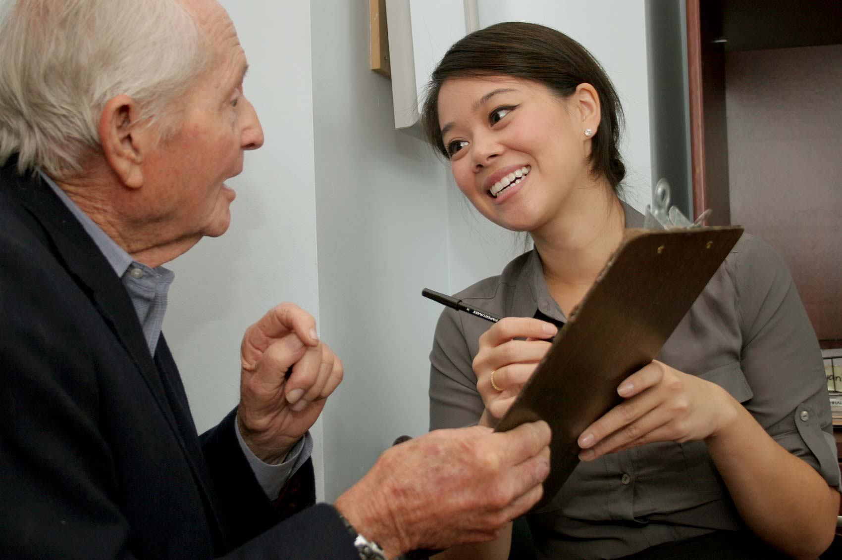 Female medical office staff member smiling while talking with patient